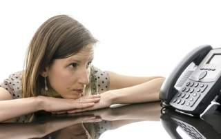Woman waiting for a phone call while looking at telephone