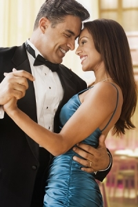 Hispanic couple dancing in eveningwear