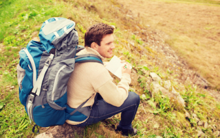 adventure, travel, tourism, hike and people concept - smiling man with backpack sitting on ground