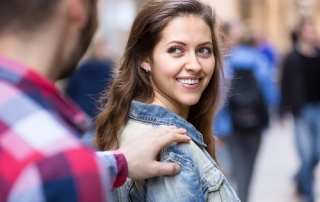 Young man stops a beautiful happy woman on a street to pick her up