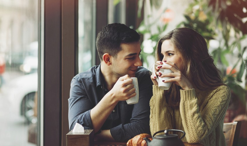 Enjoying fresh coffee together. Beautiful young couple talking to each other and smiling while enjoying coffee in cafe together