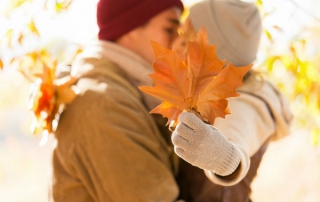 young couple kissing behind autumn leaves