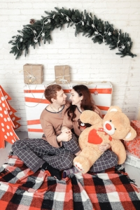 Loving young couple sitting on floor by christmas tree at christmas morning, caressing.